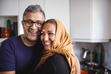 Portrait of happy man with woman in kitchen at home