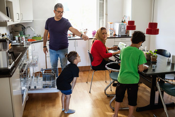 Family of four in brightly lit kitchen