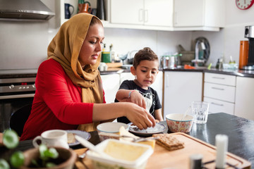 Mother and son having breakfast at dining table in kitchen