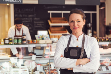 Portrait of confident owner standing arms crossed while colleague working in background at grocery store