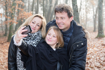 happy family in park making selfie picture with smartphone