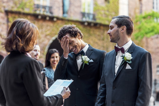 Gay man looking at shy partner while standing in front of priest during wedding ceremony
