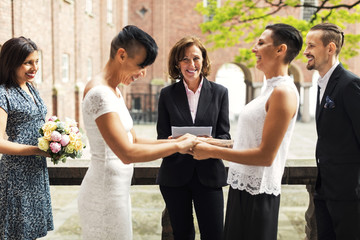Priest and guests looking at cheerful lesbian couple holding hands