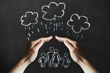hands protects a family from the elements - rain or storm
