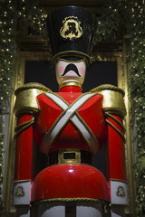 Bright red Christmas nutcracker ornamental soldier standing under twinkling Christmas lights