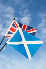 Scottish and UK Union Jack flags flying together in bright blue sky
