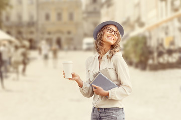 Urban literature / Happy young student with a coffee-to-go, holding books for reading and studying against urban city background.