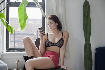Young woman using smartphone while sitting by window at home