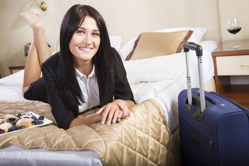 Smiling young business woman lying in her hotel bed.