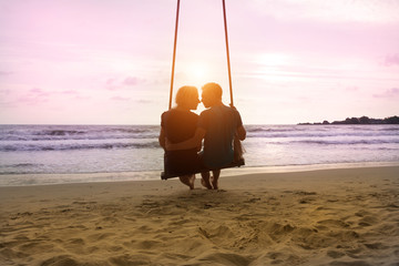 Romantic couple is sitting and kissing on sea beach on rope swing and looking at sunset horizon. Family vacation on honeymoon