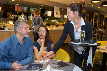 Waitress serving drinks to couple in restaurant