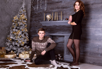 Young happy couple sitting in front of christmas tree