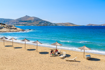 Sun umbrellas on sandy beach in Naoussa town, Paros island, Greece