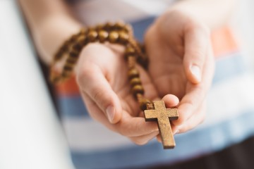 Little boy child praying and holding wooden rosary. Fototapete