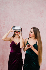 family and technology. Two pretty twins in evening dresses, one with smartphone, another wearing virtual reality glasses.