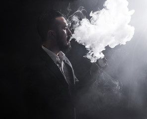 Men with beard vaping on black background