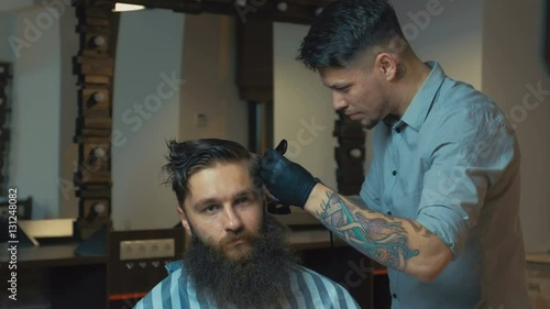 Unparalleled Barber With A Beard And A Tattoo Is Cutting The