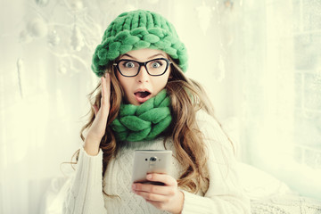 Indoor portrait of young beautiful surprising girl looking at camera and holding smartphone. Model expressing joy and excitement with hand and face. Woman wearing eyeglasses, trendy green accessories