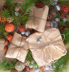 Christmas gifts in craft paper package tied a rope on wooden background in a frame christmas tree branches decorations.