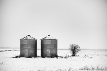 Two flat bottom steel grain bins in a rural black and white winter landscape