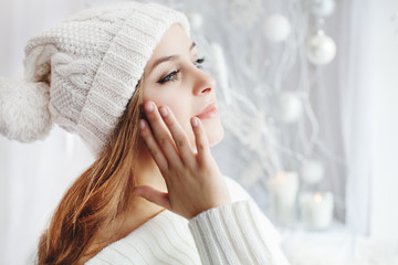 Indoor close up portrait of young beautiful girl touching her face, looking aside. Model wearing winter hat and sweater. Day light from window, white room as background. Copy space for text