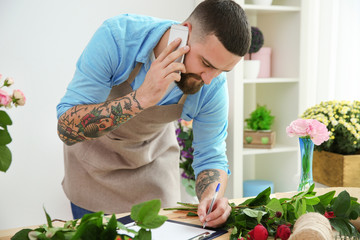 Handsome florist accepting order by mobile phone