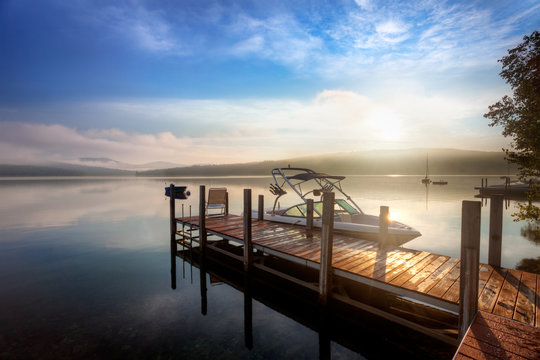 Sunrise through the clouds and mist over a calm New Hampshire lake