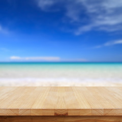 Wood table top on blurred beach background.