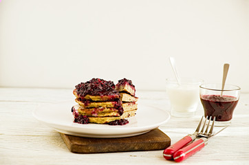 Pancakes stack with banana, coconut flour and blueberry jam on a white plate.  Bright healthy breakfast. White wooden table
