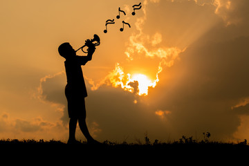 children playing trumpet background of sunset