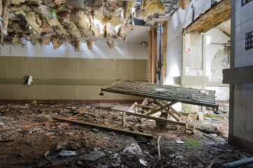 A broken rusty hospital bed,discarded underneath a collapsing asbestos roof, in an abandoned hospital. Exploring urban decay.
