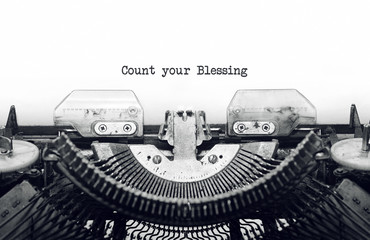 Vintage typewriter on white background with text Count your Blessing