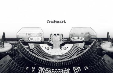 Vintage typewriter on white background with text Trademark.