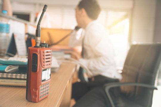 Walkie-talkie radio on wooden table operator in office.
