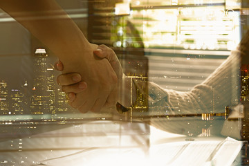 Double exposure of businessman and businesswoman handshake after