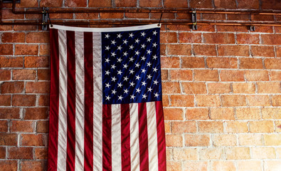 American Flag Hanging on the Brick Wall with Copy Space