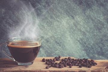 Black coffee with coffee bean on wood table