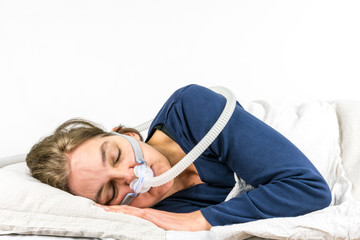 Woman sleeping  on her side with CPAP, sleep apnea treatment. Studio portrait white background.