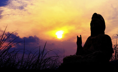 Kuan Yin buddha  on sunset with sky background with soft-focus in the background. dark   tone and over light