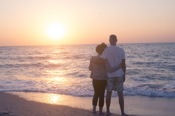 Coupleon on beach hugging and admiring  sunset