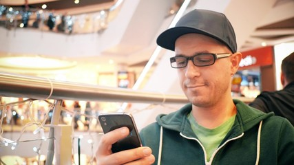 Young caucasian man wearing cap and black rim glasses taps on his mobile phone touchscreen in a cafe