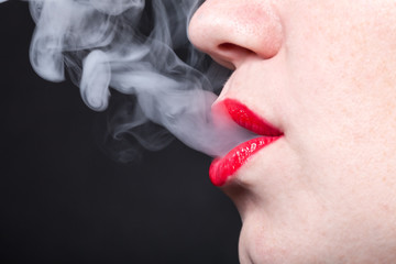 Profile view of a woman with vapor escaping from her lips
