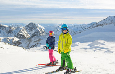 Happy  children  enjoying winter vacations in mountains . Ski, Sun, Snow and fun.