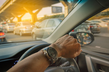 Closeup left hand driving on traffic jam background, Business Co