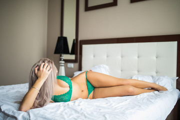 Sexy blonde girl in green lingerie in bed at home