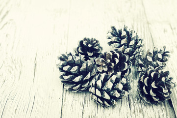Pine cones on a white old wooden surface. Preparation by new year, a festive background