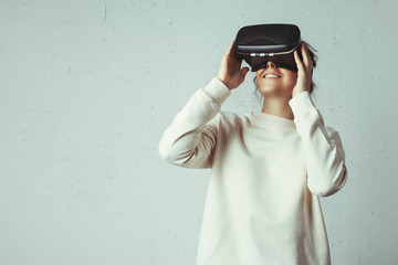 Handsome young woman wearing virtual headset. Smiling hipster using VR glasses. Blank sweater. White grunge wall with cracks background