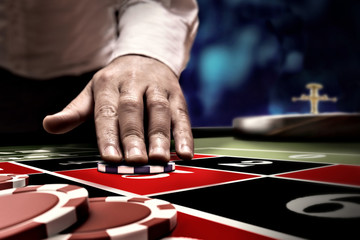 gambler bet on roulette at casino table