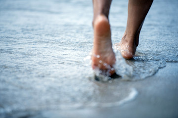 Woman barefoot walking on the beach