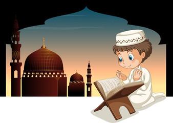 Muslim boy praying with mosque background